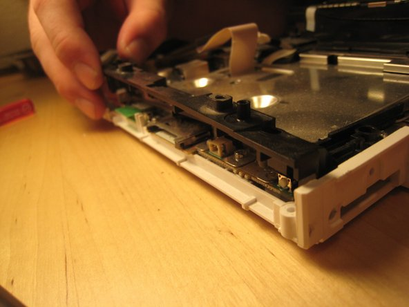 We begin trying to get to the logic board by removing this small black plastic rim.