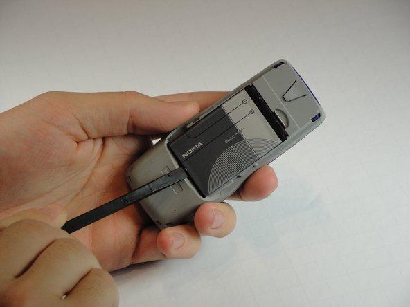Calez l'extrémité plate du spudger dans le petit retrait à côté du logo Nokia sur la batterie.