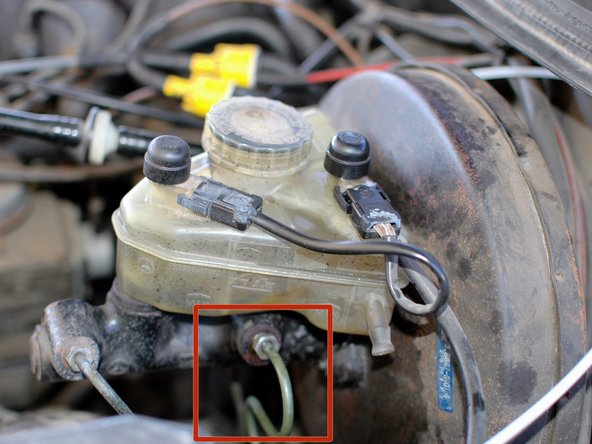 Under the hood, locate the connection for the driver's side front hard line on the master cylinder, just below the brake fluid reservoir. The line is the rear line on the driver's side of the master cylinder.