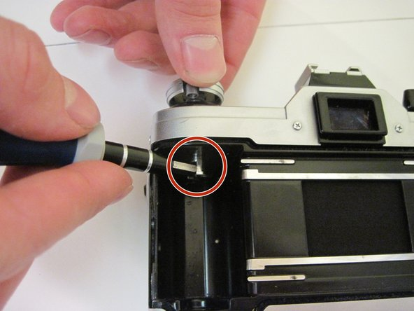 Open the film compartment and place the screwdriver in the the slot to keep the shaft from moving.
