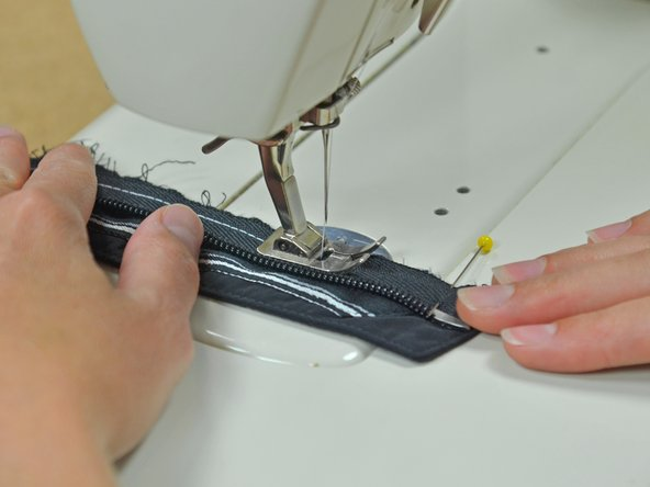 Backstitch at the end of the zipper to prevent the seam from unraveling.