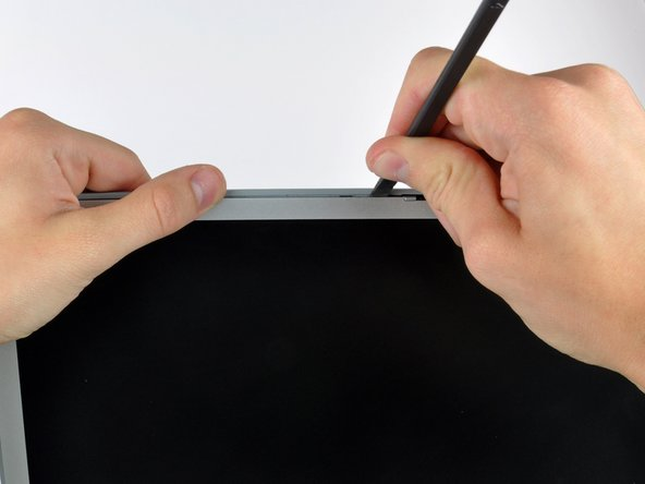 Insert a spudger just to the left of the hinge opening on the top edge of the display between the front display bezel and the plastic strip attached to the rear bezel.
