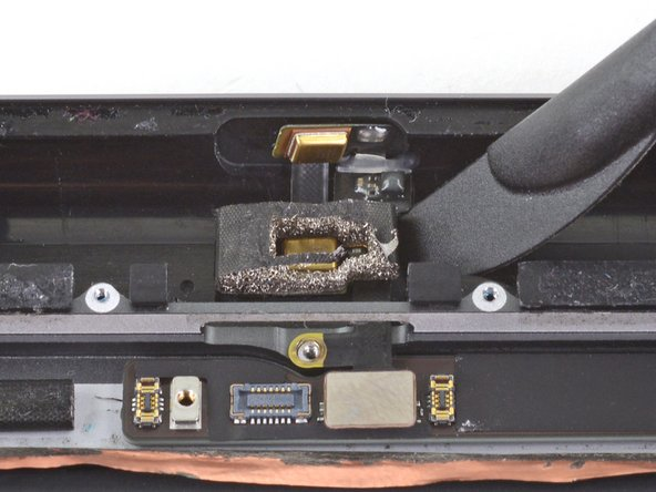 Insert the halberd spudger underneath the lower microphone and twist to peel it away from the rear case.