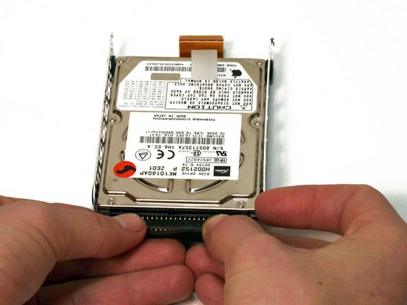 Pull the connector cable out from the hard drive, applying even pressure while gently rocking up and down.