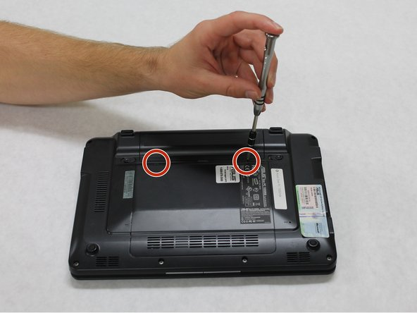 """Use a #00 Phillips Head screw driver to remove the two 1/4"""" screws that hold the back panel in place."""