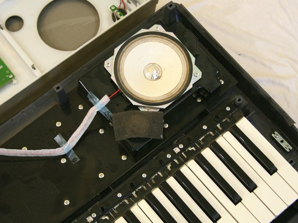 Remove the translucent blue tape that holds the speaker wires to the keyboard.