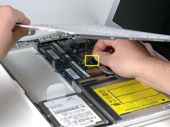 天板を持ち上げながら、銀色のケーブルのコネクタ部分の黒いタブを上に引っ張ってコネクタを外してください。