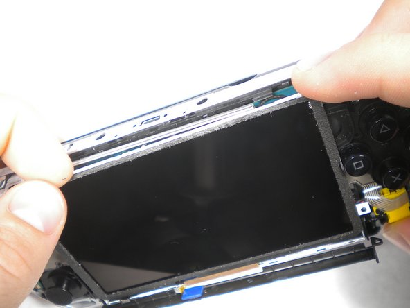 Slowly lift the LCD screen off the PSP starting at the top edge corner.