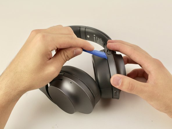 Start by inserting the iFixit plastic opening tool in the crease between the hard plastic and the ear cup, and then gently apply pressure until it separates. You may need to repeat the process on back until it is completely separate.