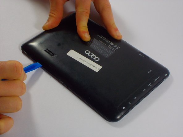 Carefully, wedge the plastic opening tool in-between the seam that separates both halves of the tablet.
