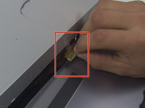 Unease the yellow connecting tape with the spudger at the bottom of the screen.