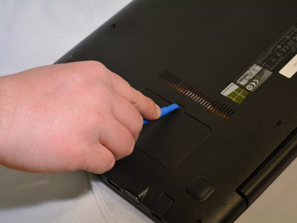 Use the plastic opening tool to open the RAM cover.