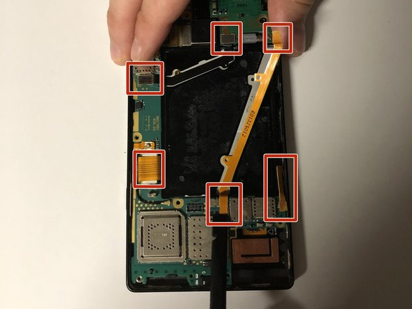Use the flat end of a spudger to disconnect the six ribbon cables from the motherboard.