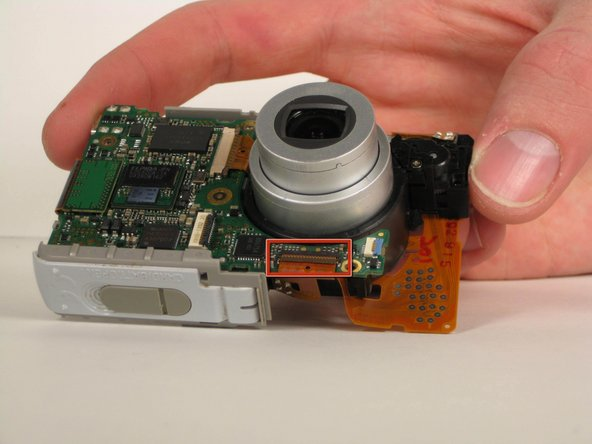 Locate the black ZIF connector located directly below the lens.