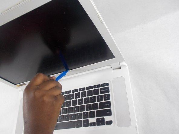 Calez l'un des outils d'ouverture en plastique à l'intérieur du couvercle de l'écran et faites-le glisser sur le périmètre intérieur de l'écran.