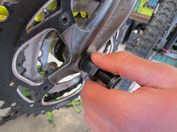 Screw the larger diameter threads on the crank puller into the hole you removed the cap from.