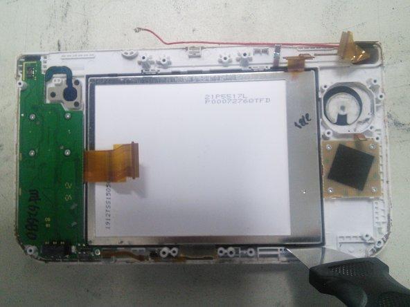 Glisser un outil plat entre le support noir du LCD/Tactile et le carter de la console puis soulevez le doucement. Glissez ensuite un métronome dessous pour le maintenir.