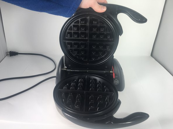 Pull the handle up and away from the waffle iron to remove the cover and expose the circuit.