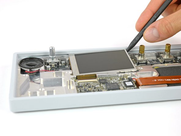 The display is held in place with a mild adhesive. A spudger helps you to get it free.
