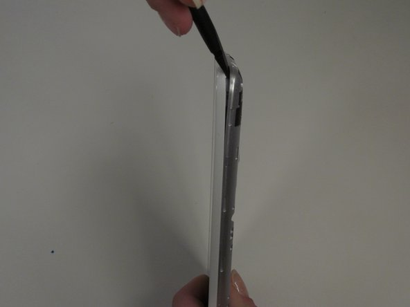 Use a plastic spudger tool to pry away the cover by placing it between the cover and the phone.