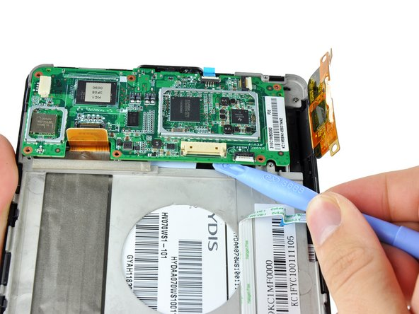 Use a plastic opening tool to gently lever up the bottom side of the motherboard to free from the adhesive on its underside.
