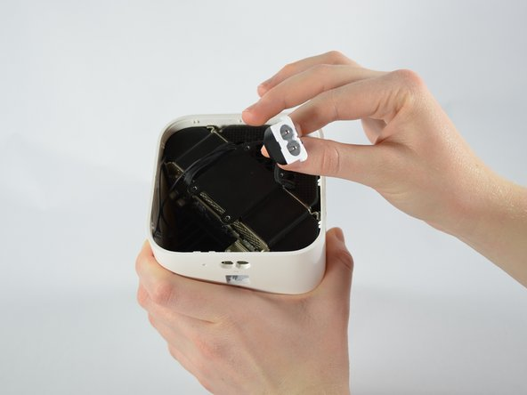 Using two fingers, pinch the power supply wire and gently lift it upward. Move it away from the metal plate.