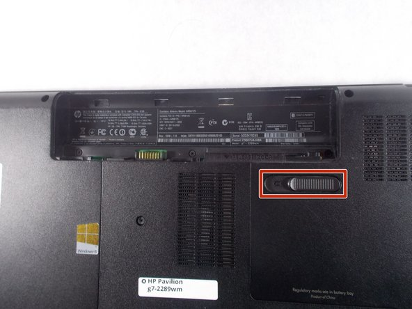 Slide the battery release latch to the left, towards the center of the laptop.