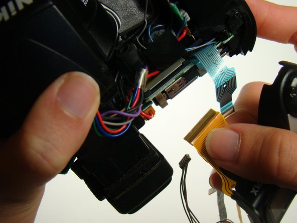 Unplug the orange ribbon and the  other wires and finish carefully removing the top panel.