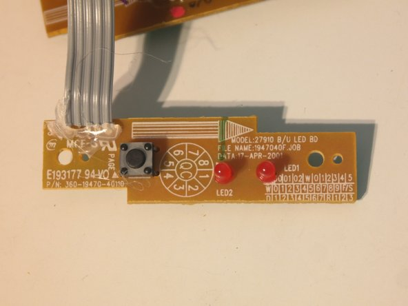 The button board contains a lonely button, 2 LEDs, and is connected with a soldered ribbon cable reinforced with hot glue.