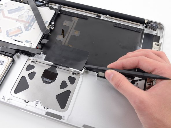 Use the flat end of a spudger to peel up the edge of the large piece of black tape covering the trackpad cable.
