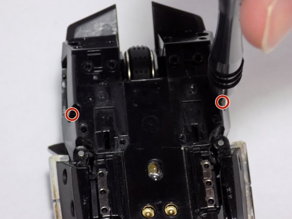 Using the T6 Torx screwdriver, remove the two 4mm screws hidden in the deep holes indicated in the first picture.