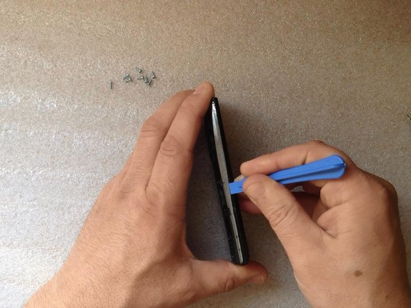 Use a Plastic Pry or other plastic tool to unhook the back housing / bezel and remove it.