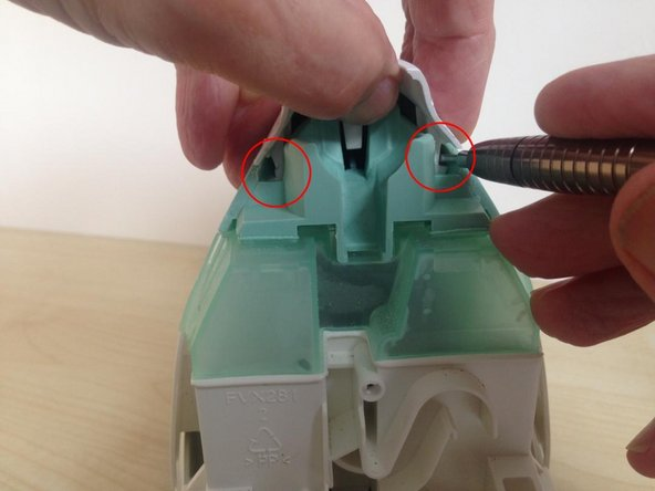 Whilst lifting the rear of the top cover with one hand, release two clips, one each side, which retain it.