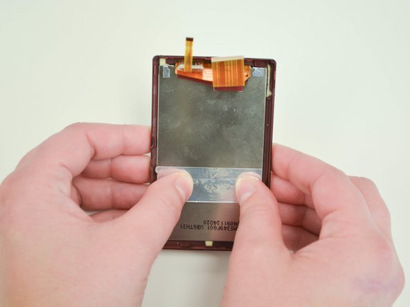 Remove the screen from the case of the camera by carefully pushing on the back of the screen.