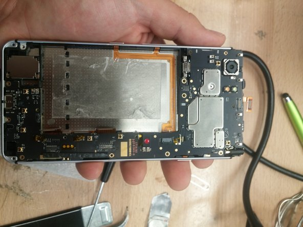 With all screws and brackets removed and all flex cables disconnected you can now remove the motherboard. I recommend starting at the top (Rear facing camera side) and removing the board top down because the charging port sits in the frame of the phone and will come out more easily last.