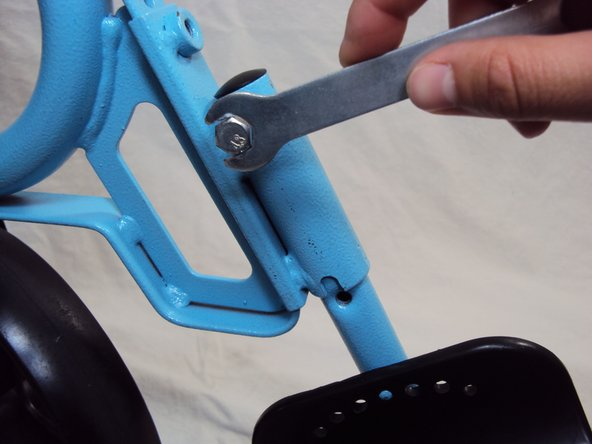 Screw in the bolt to the top socket to secure the height of the footrest.
