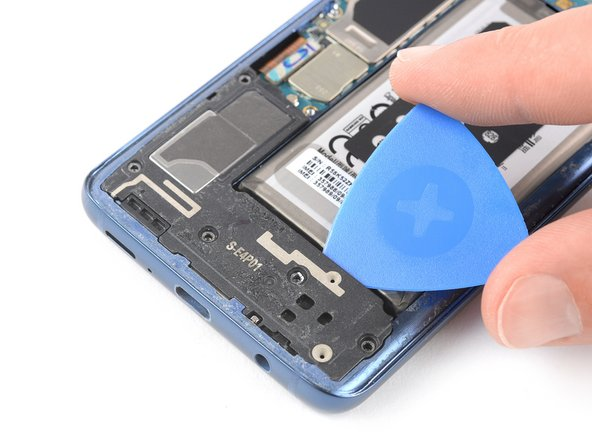 Insert an opening pick underneath the top edge of the loudspeaker assembly.