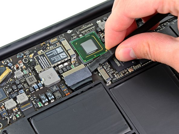 Use the flat end of a spudger to pry both short sides of the battery connector upward to disconnect it from its socket on the logic board.