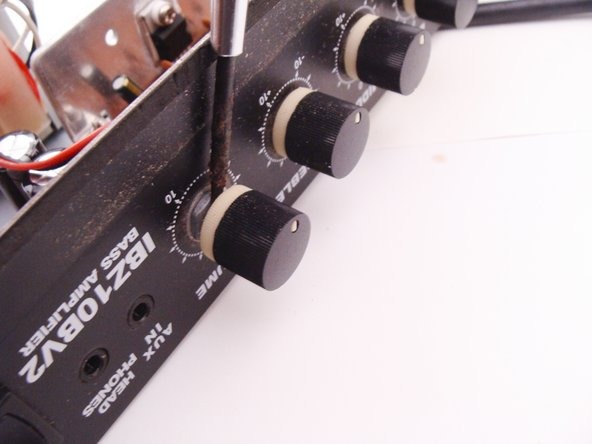 To remove the amplifier board from the chassis, you will first need to remove the volume and tone control knobs