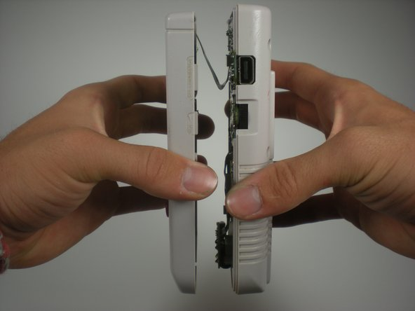 Carefully lift up the top half of the system. Be careful, there's a ribbon cable that connects the top and bottom half of the system.