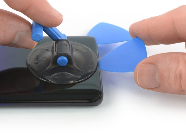 Insert a second opening pick and slide it to the bottom left corner  to cut the adhesive.