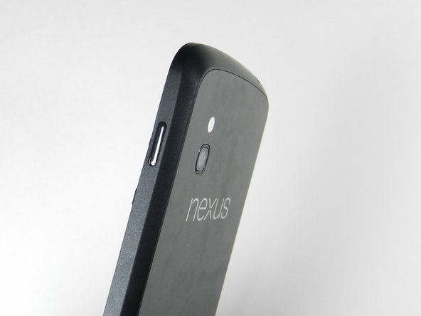 Holding the back case, gently push the power button in towards the center of the phone using a spudger.