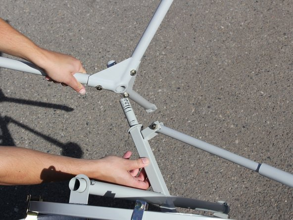 Attach the top of the center plate of the tripod base stand to the cross bearer bar making sure the flat side of the tripod legs points away from the solar panel dish.