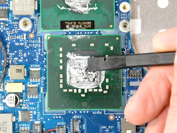 Use the flat end of a plastic spudger to remove any solidified thermal paste from the surface of the processor(s).