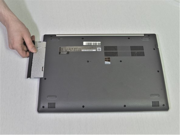 Carefully remove the optical drive bracket by pulling the bezel away from the laptop.