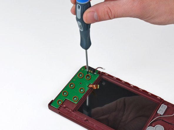 Remove the seven Phillips screws securing the battery/control board to the upper case.