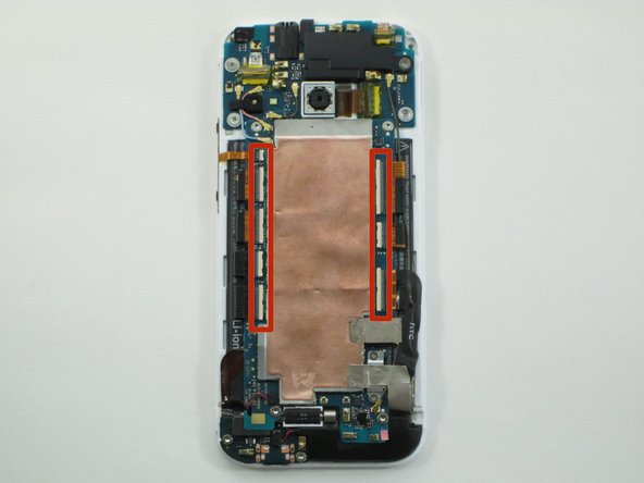 Using the flat end of the spudger, pop up the white tabs on all ribbon cable connectors located to the left and right of the copper plate.