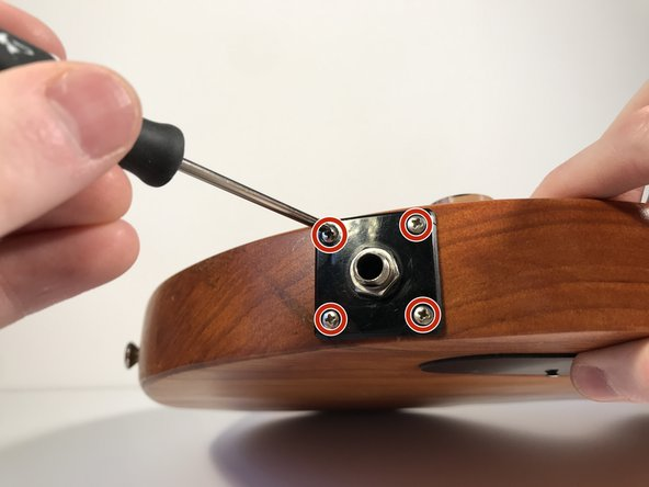 Using a Phillips #1 screwdriver, remove the four 7 mm screws  holding the input jack cover.