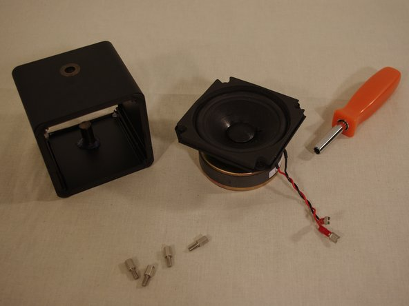 Remove the four silver bolts holding the speaker in place.  These bolts also have threads inset for the grill screws to fit into.