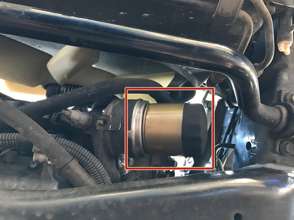 Locate the oil filter. It is on the driver's side of the oil pan and above the steering linkages.